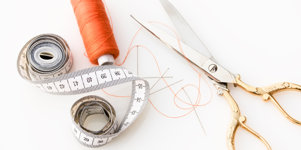 Sewing Kit of scissors, orange thread, tape measure, needle and pins on a white background