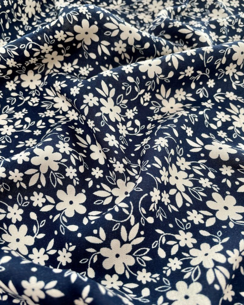 Navy blue viscose fabric with sand coloured flowers and leaves.