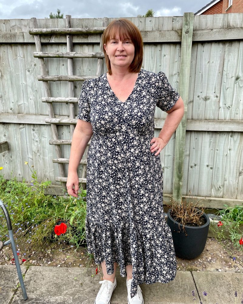 A lady standing in a garden in front of a fence wearing a navy floral viscose dress made using pattern Simplicity 8875