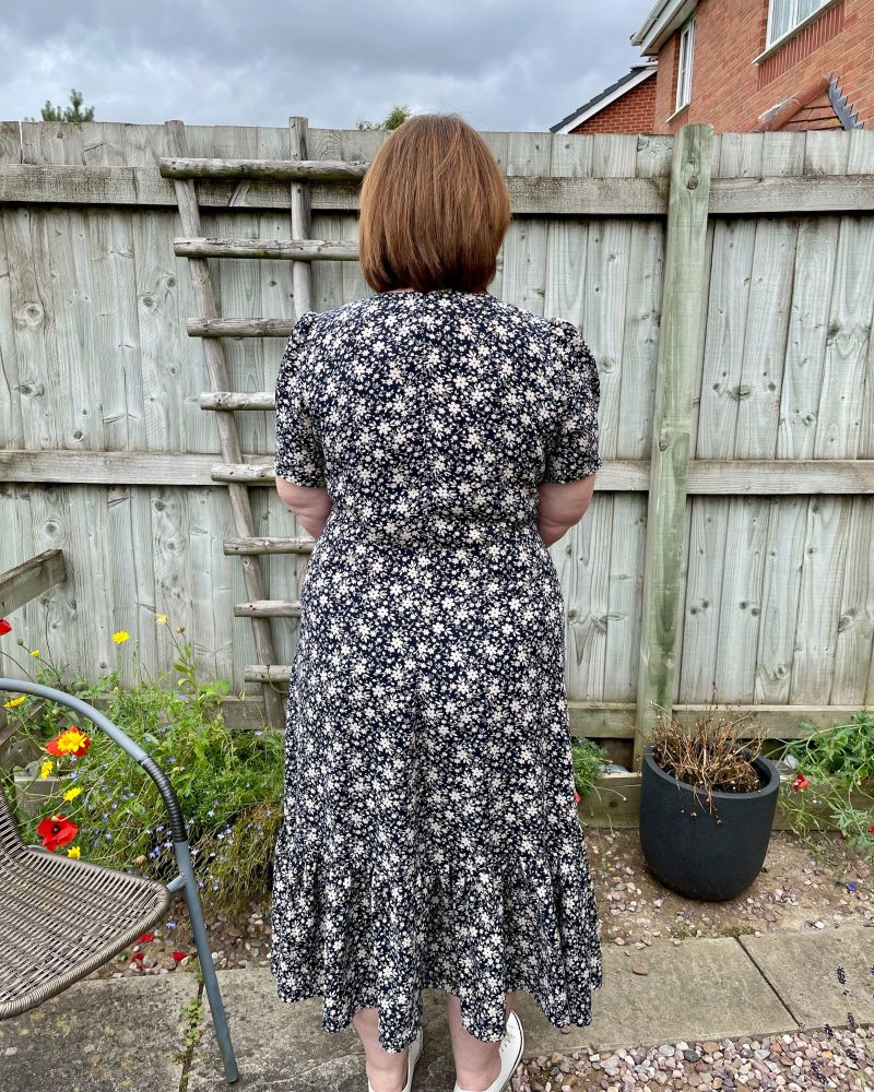 A lady wearing a navy floral dress made using sewing pattern Simplicity 8875 showing the back view and standing in front of a garden fence.