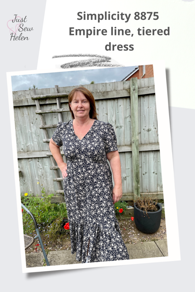 A poster of a lady wearing a dress made using sewing pattern Simplicity 8875. Made with navy and sand flowered fabric, the lady is standing in front of a garden fence
