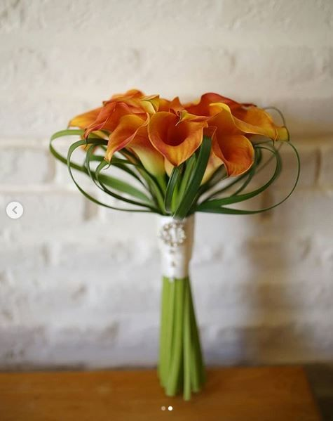 Brides bouquet of orange calla lilies with Grandmothers brooch