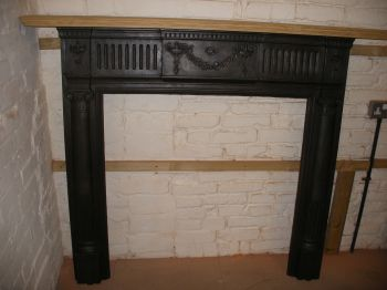 Reclaimed Victorian cast iron fireplace surround with stripped pine shelf.