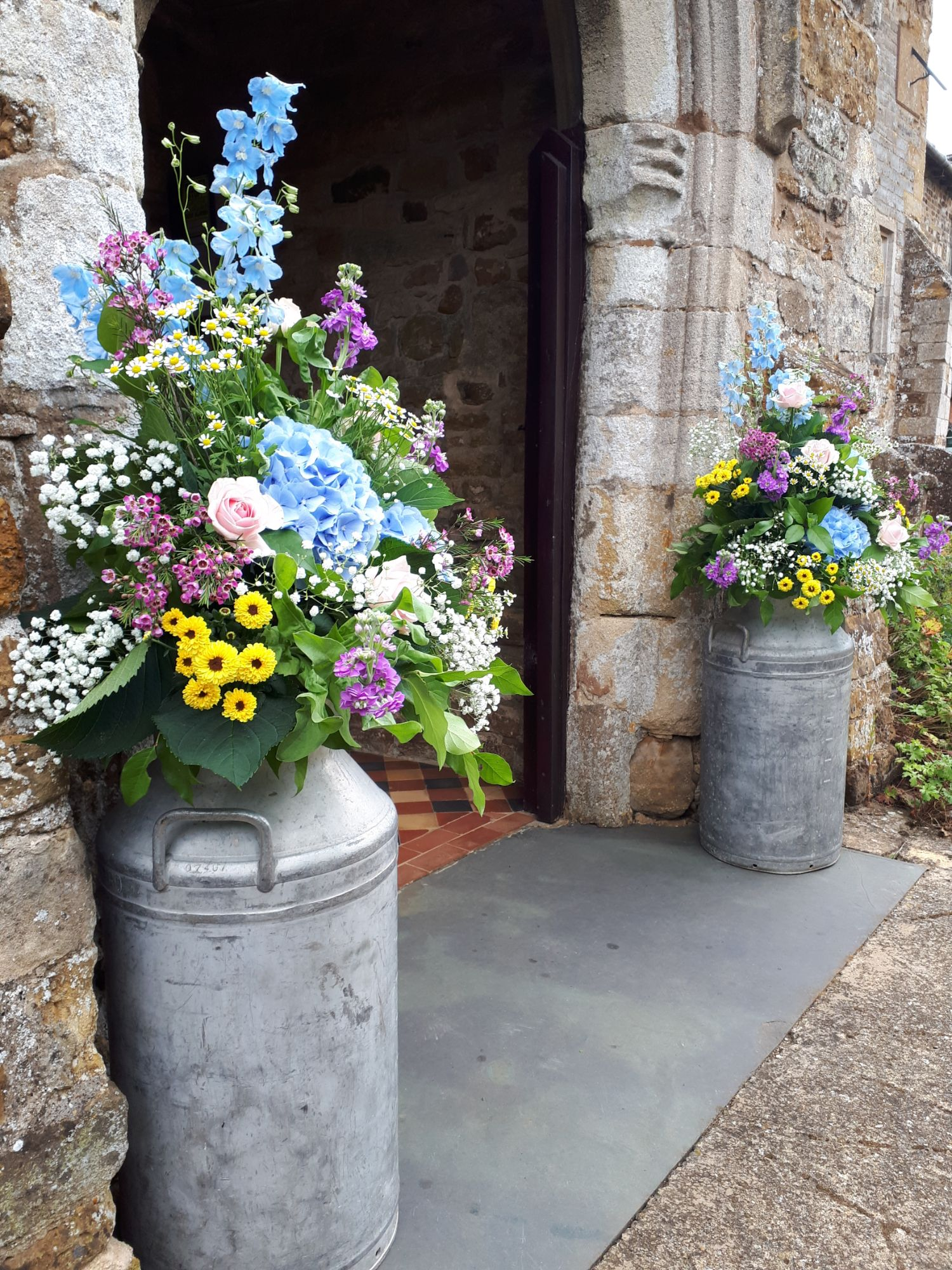 Church flowers in milk churns
