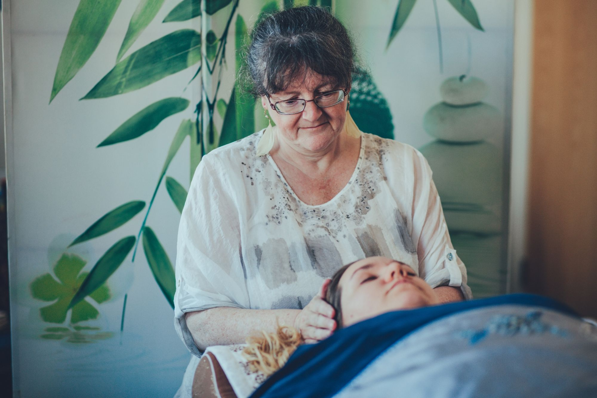 Helen giving a woman a Reiki treatement