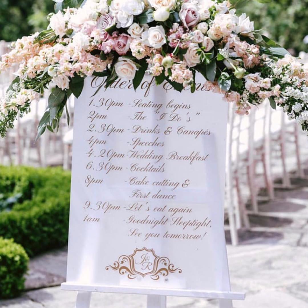 frosted acrylic order of events with gold detail and wedding monogram