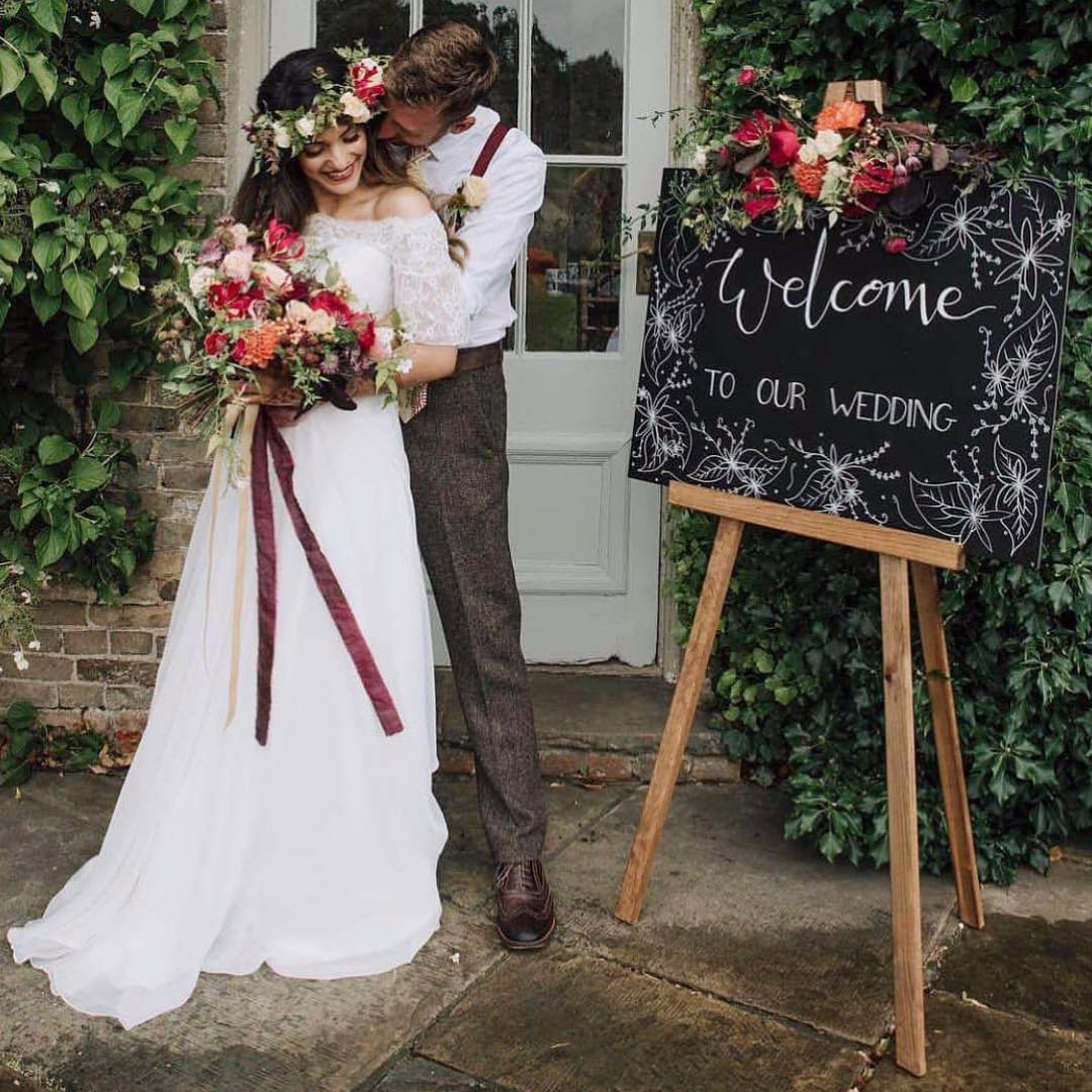 Chalkboard wedding welcome sign with hand written modern calligrpahy and flower detail