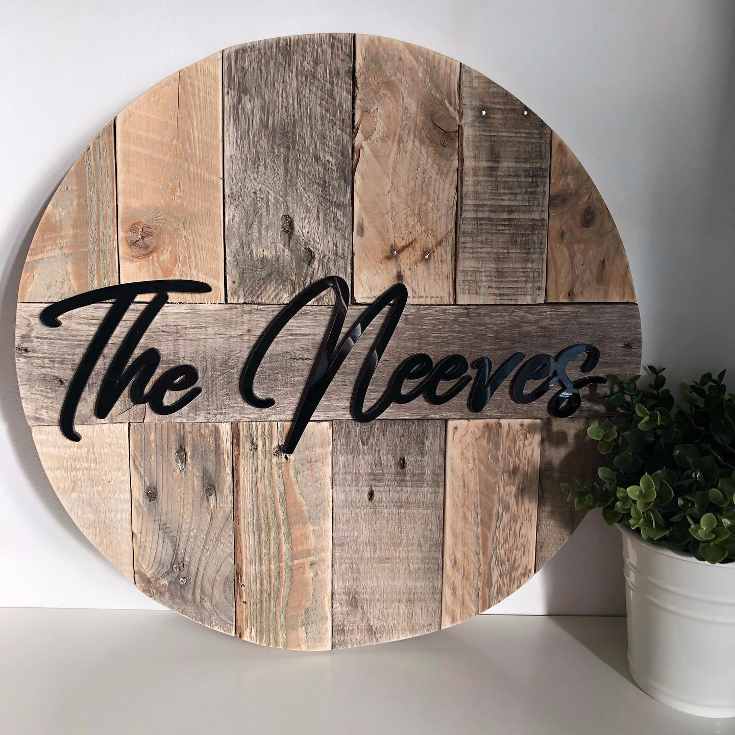 Black laser cut lettering on reclaimed pallet wood backing