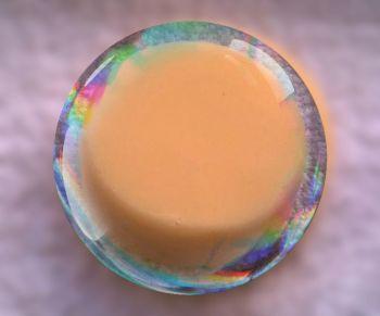Orange solid shampoo in a tin