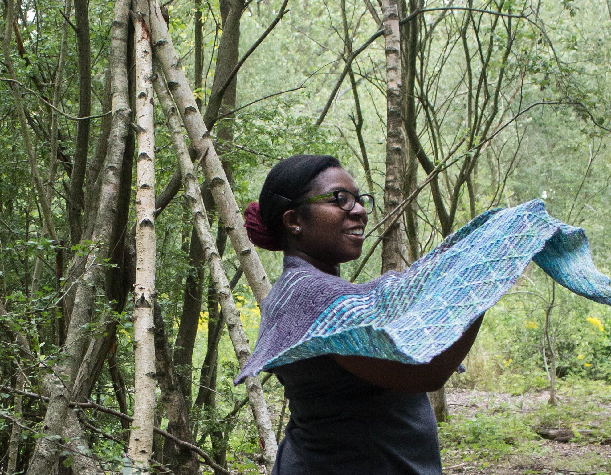 Image of a black woman smiling, holding the edge of a shawl as it floats in the wind, with the rest wrapped around her. Showing off the slipped stitch patterning and cables.