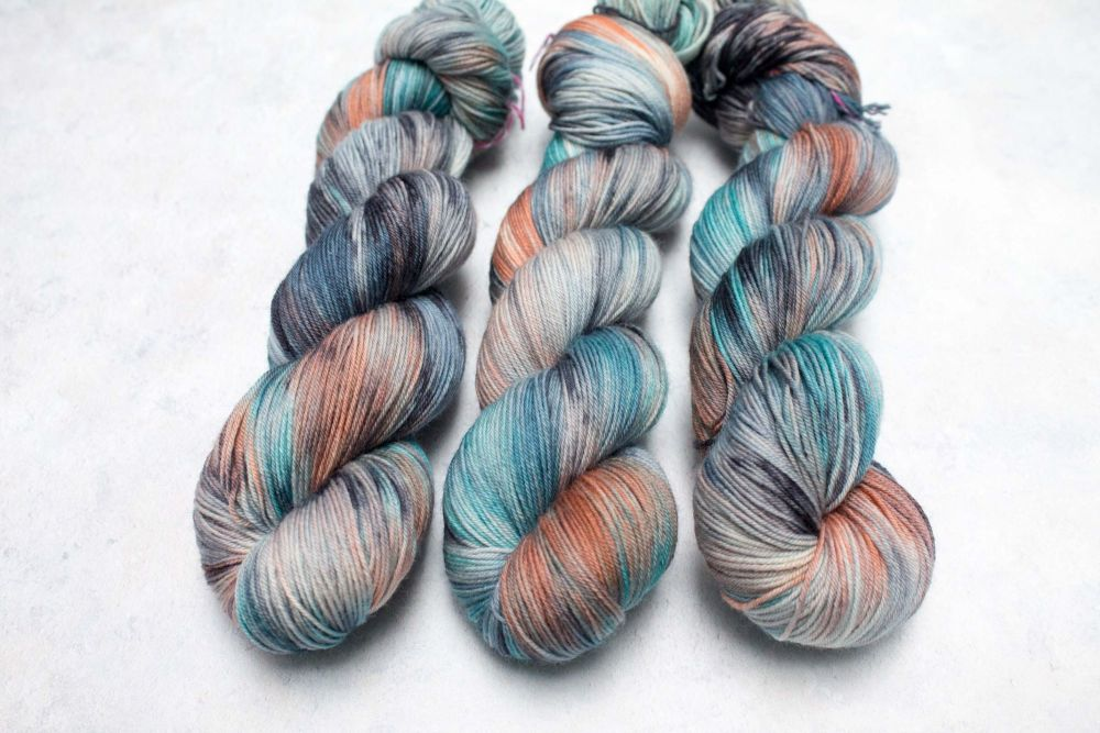3 skeins of yarn dyed with splashes of orange, teal, blue, black and mushroom