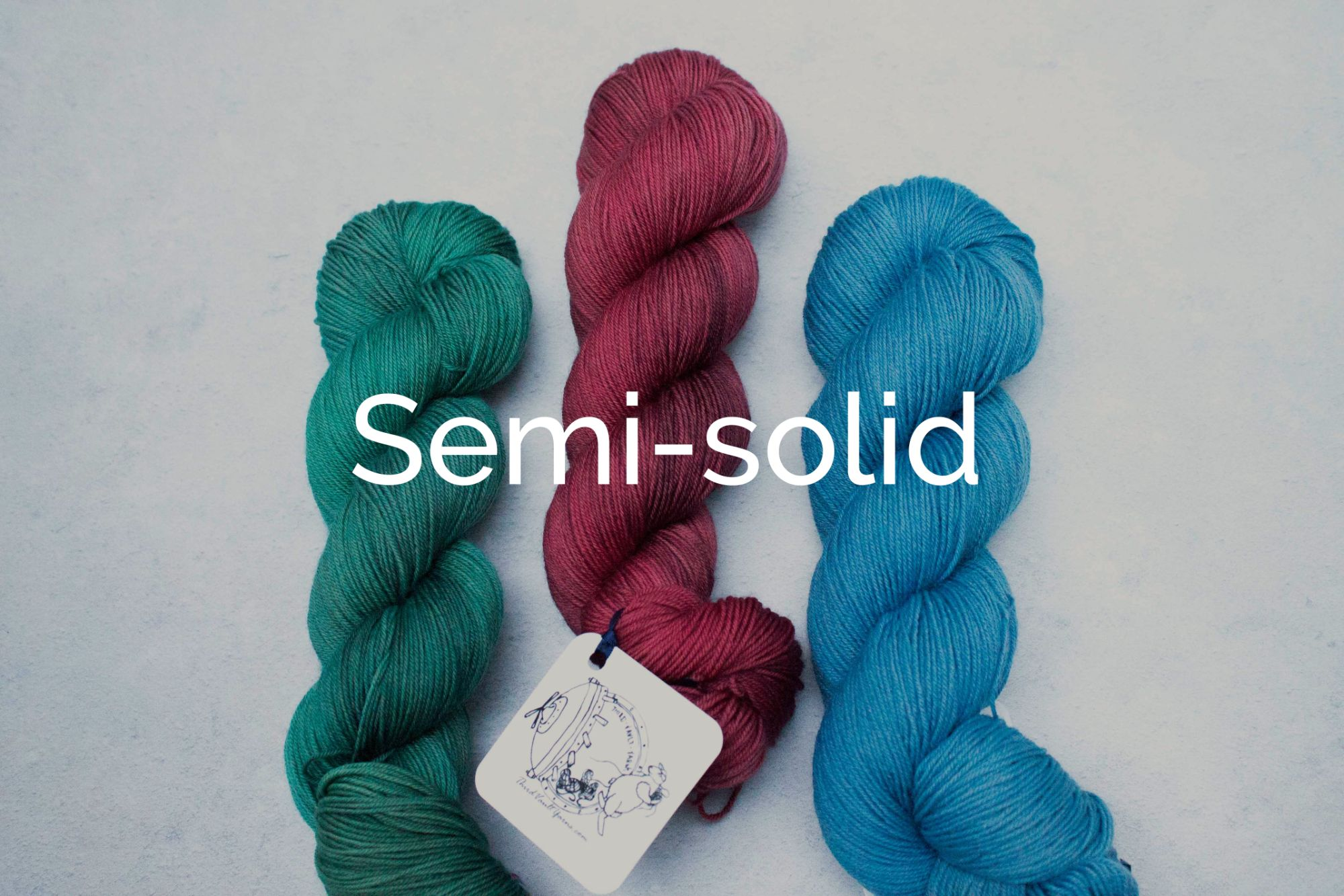 3 skeins in laid out next to each other with the middle skein offset upwards. Coloured Green, Red, Blue, with white text saying Semi-Solid (Links to the semisolid section of the shop)