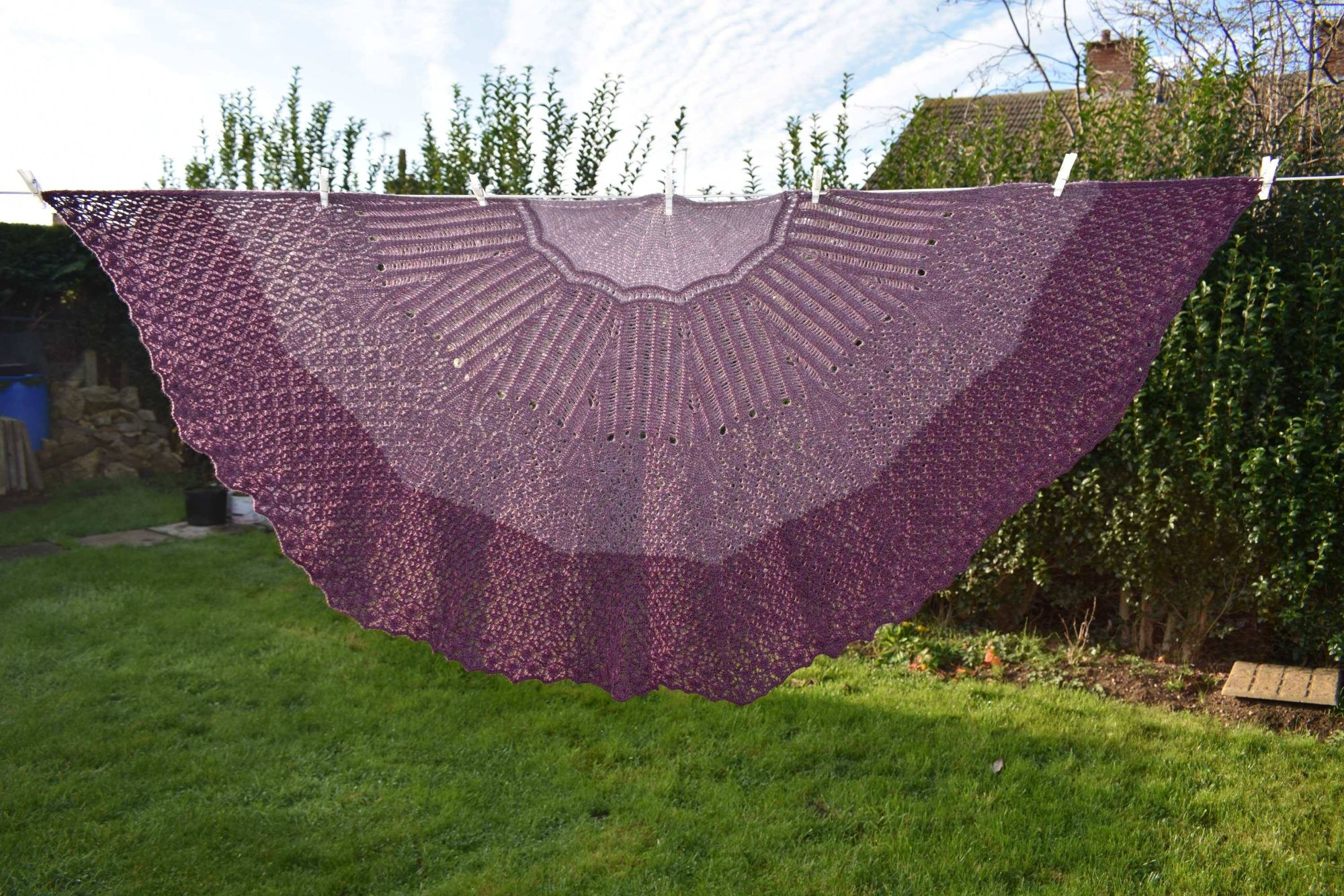 Age of Wonder shawl, hanging on a washing line, spread out, knit in different shades of purple