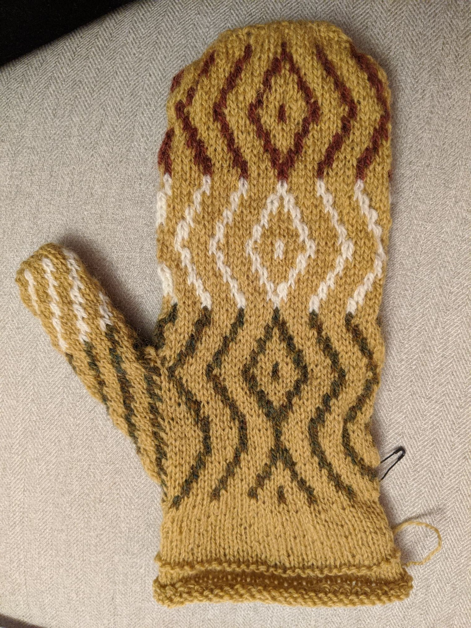 A single left mitt palm side up showing the colourwork road pattern with unfolded hem