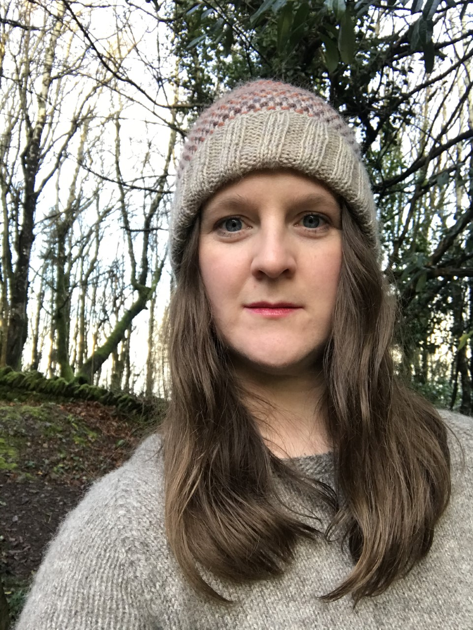 picture of helena, a brown haired white woman, staring at the camera,wearing a woolly hat, trees in the background
