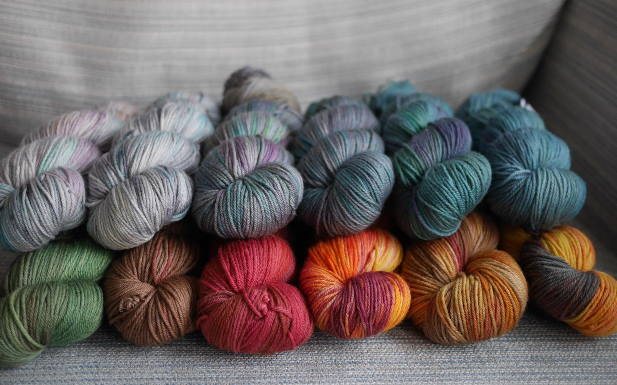 On a grey and blue striped fabric background,  12 skeins of dk weight yarn sit 2 skein high in a line. with colours ranging from silver with pastel flashes to a deep steely blue and cerulean, green and purple flashes on the top. On the bottom colours range from greens and browns to bright orangey reds with a shot of black.