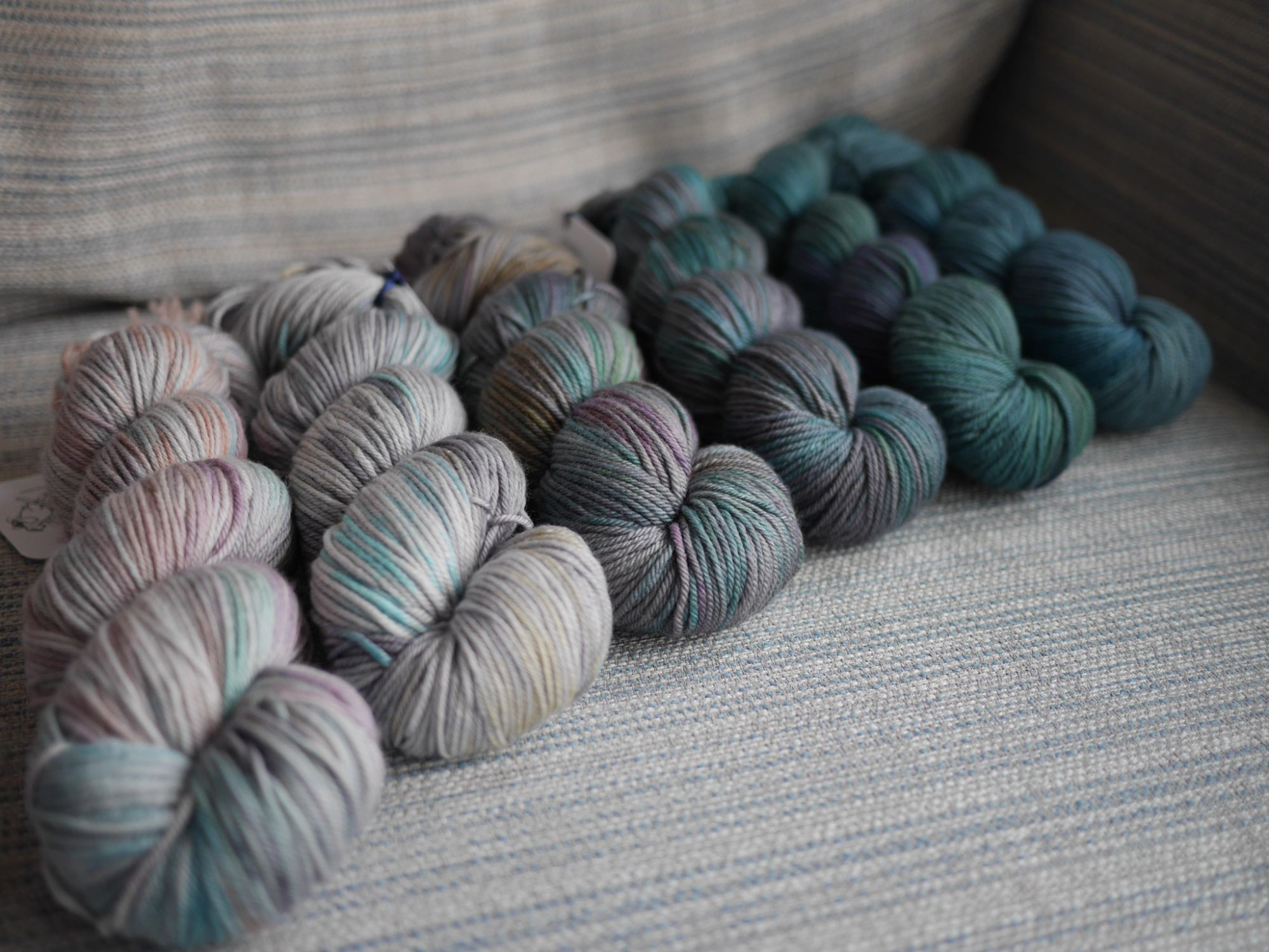 6 skeins on a grey blue striped background , at an angle colourways from left to right are the Air and Water Months in order