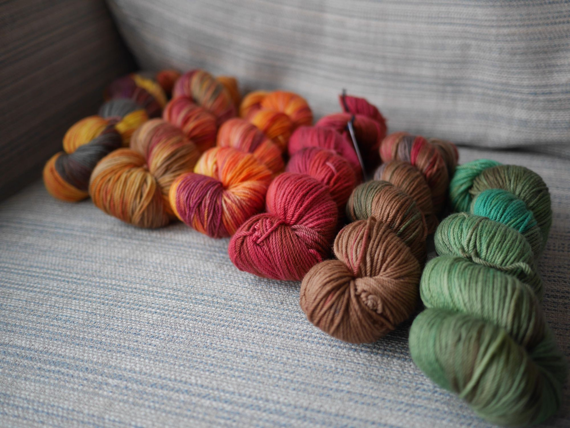 6 skeins on a grey blue striped background , at an angle colourways from right to left are the Earth and Fire Months in order