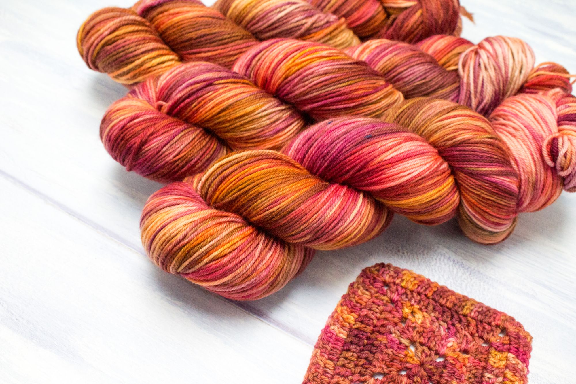 Fiery coloured yarns, with a crochet square in the yarn in the front