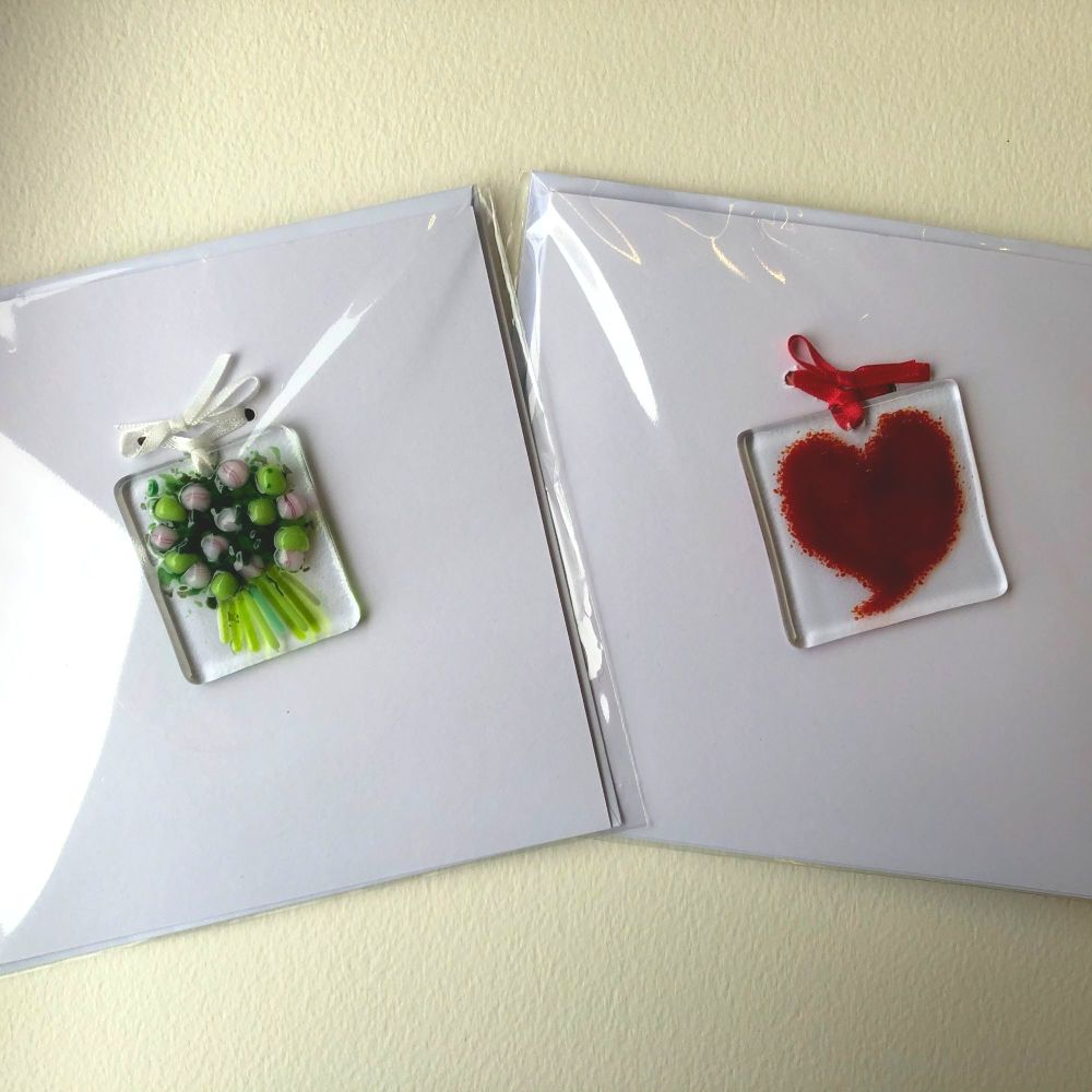 Two cards, one with a red heart and one with a pink and green flower bouque