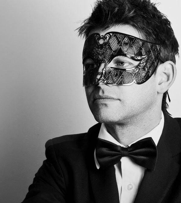 Man wearing a black filigree mask