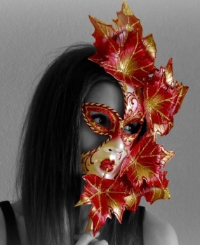 One of our designer masquerade masks in red and gold held by a beautiful girl
