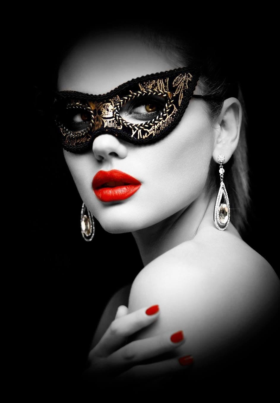 Beautiful woman with red lipstick wearing a black and gold mask