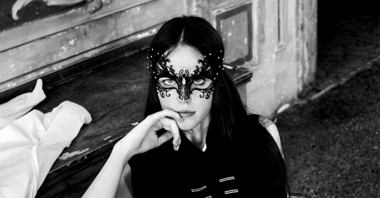 woman with black hair wearing a black filigree mask