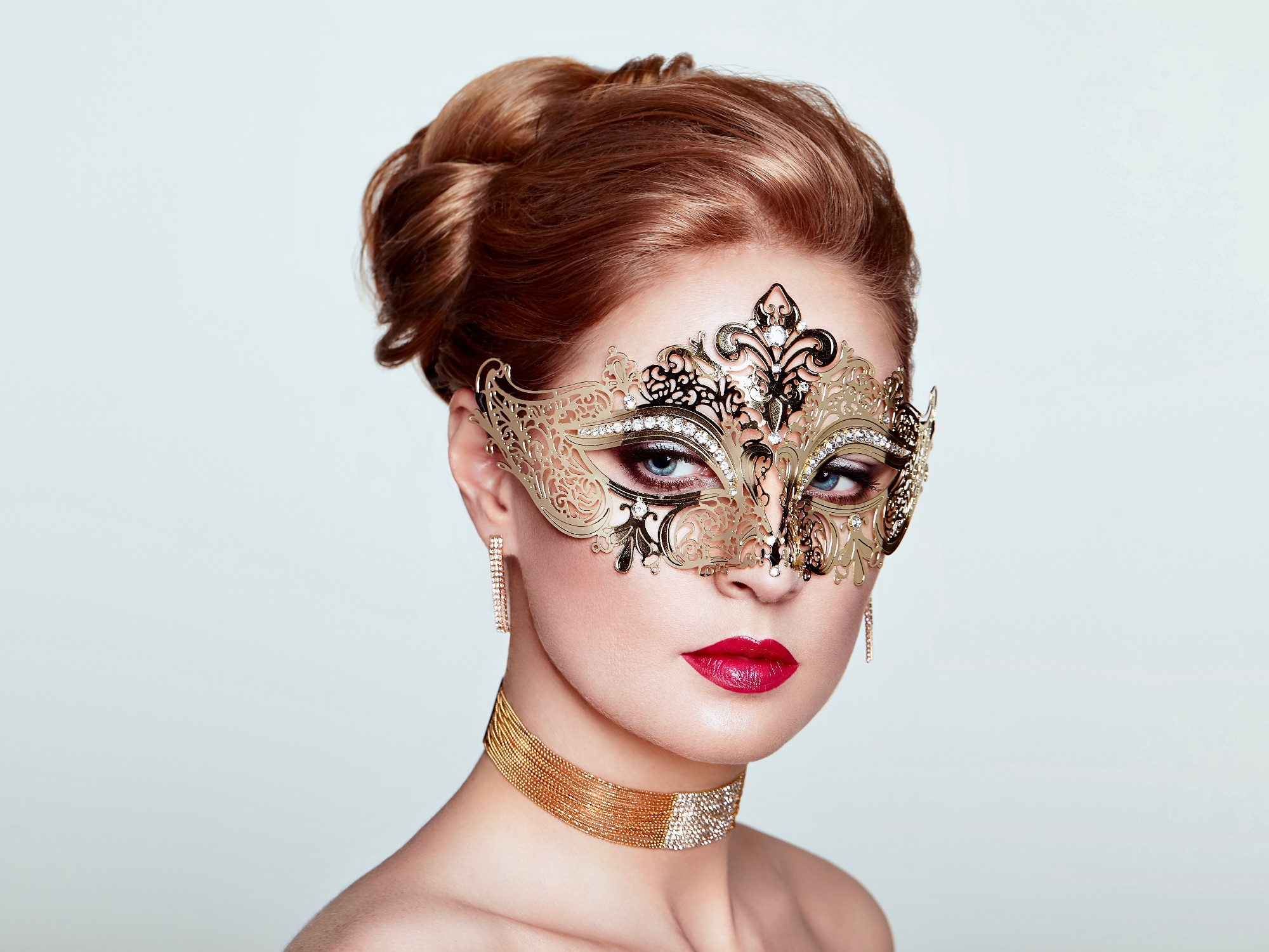 blonde haired woman wearing a gold filigree masquerade mask