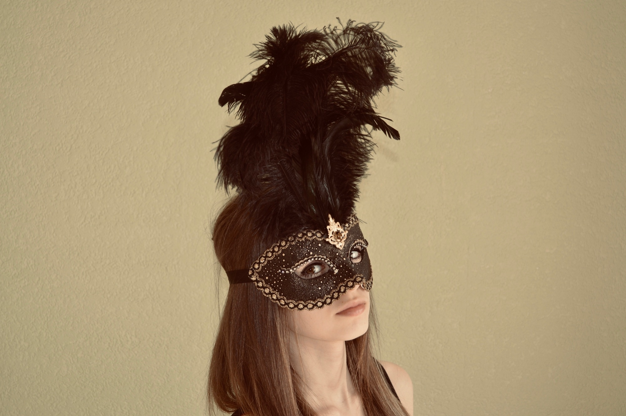 beautiful young girl wearing a black feather mask for her school project and showing what it looks like on
