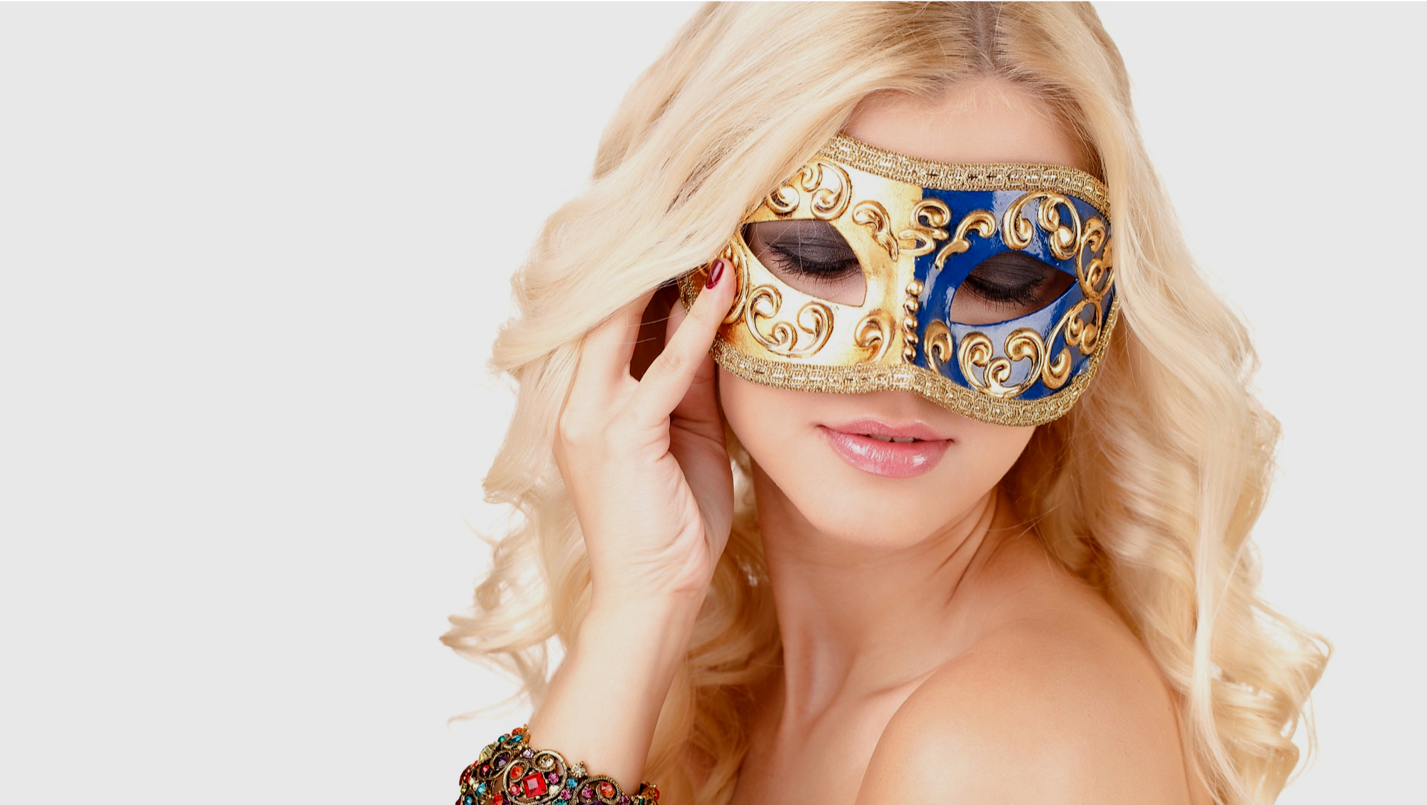 beautiful blonde woman wearing a stunning blue and gold coloured venetian mask