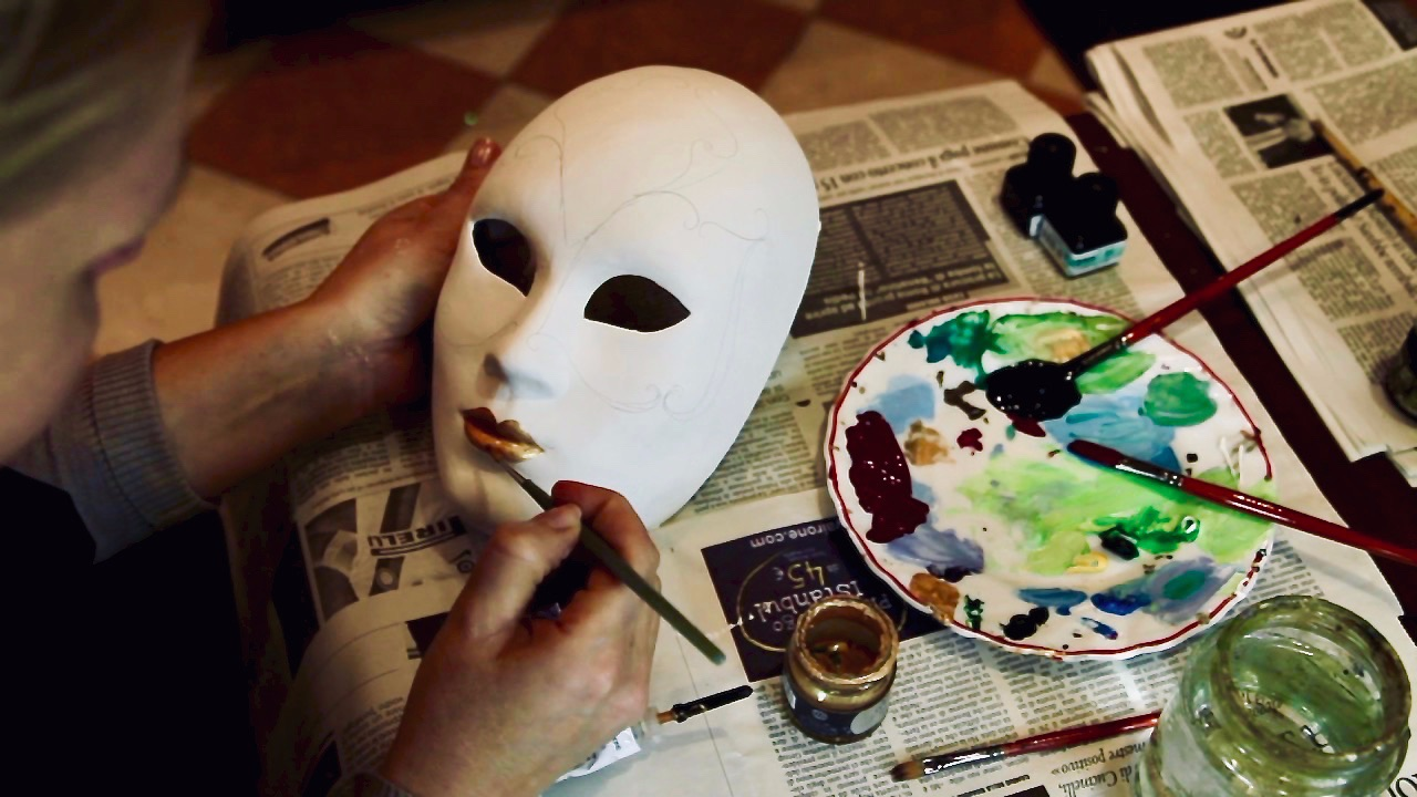 blank Full face masquerade mask being decorated and painted