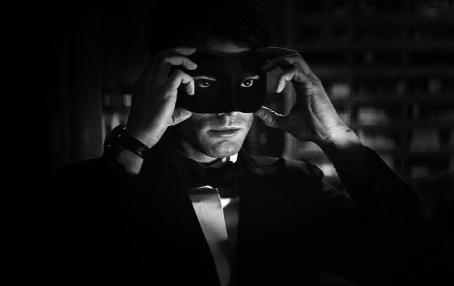 "Christian Grey putting on his black ball mask in front of a mirror in the movie ""fifty shades darker"""