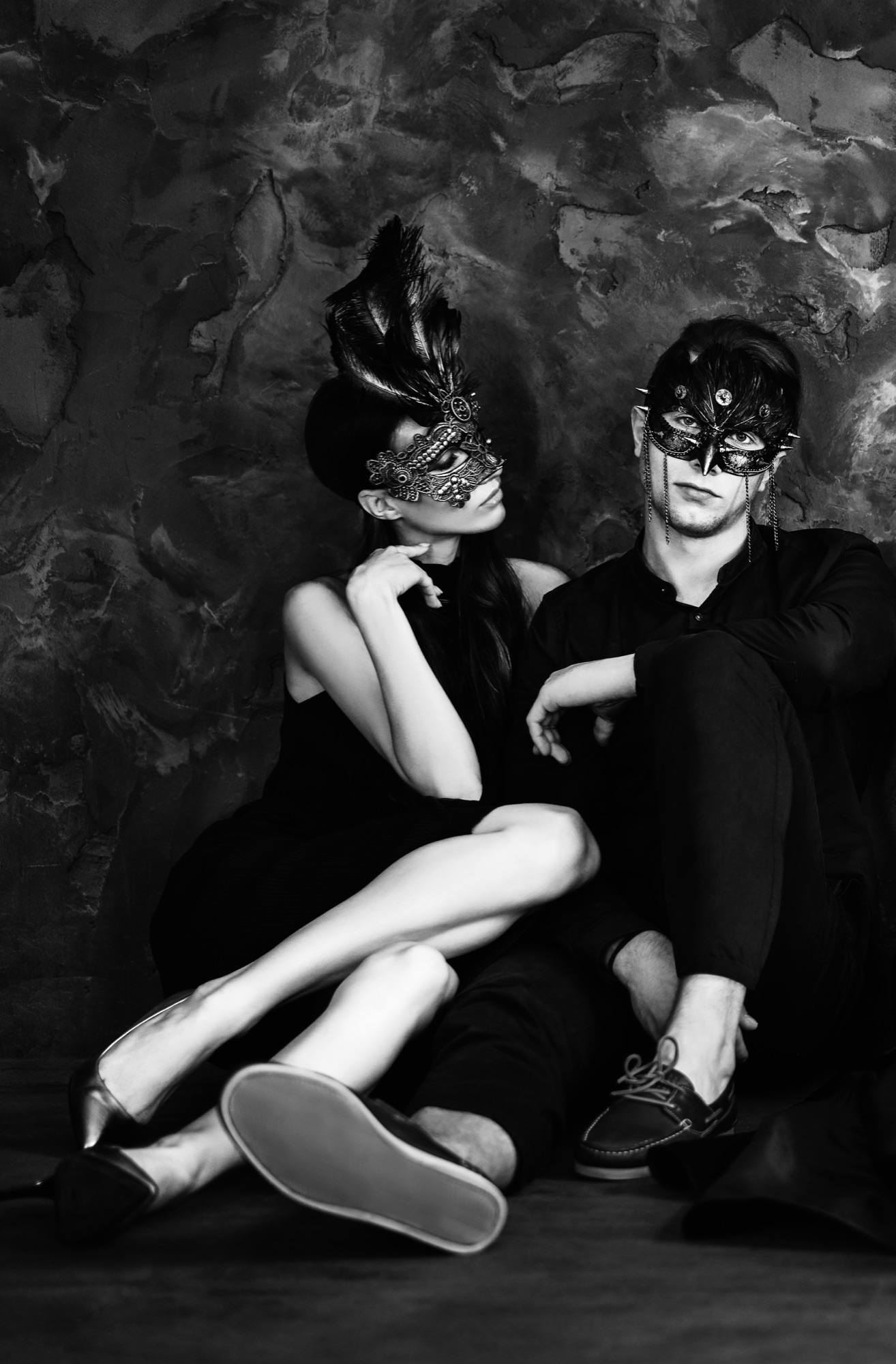 young couple sitting on the floor wearing masquerade masks