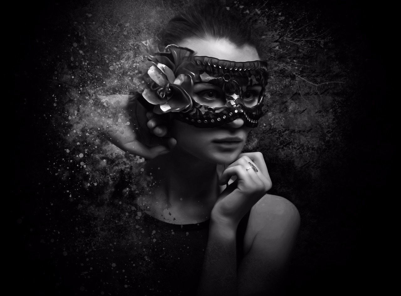 A gorgeous dark haired woman wearing a black lace masquerade mask with a side feather posing in front of a dark abstract background