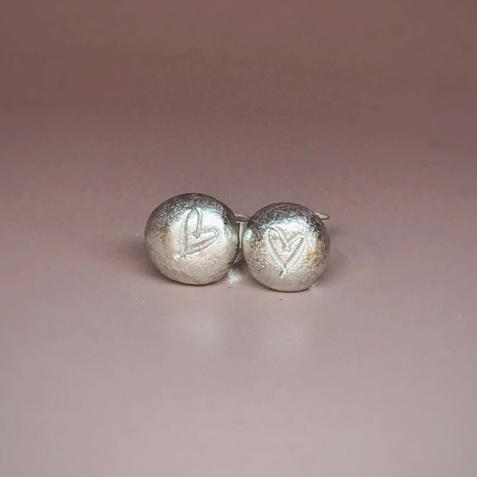Round silver stud earrings with hand stamped heart detail.