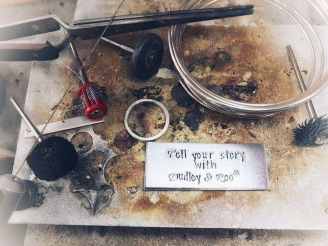 """Silversmith tools  including a jewellers saw, polishing mops and wheels, third hand tweezers, silver and a ring with a sign saying """"tell your story with Dudley & Roo"""", sitting on top of a soldering block."""