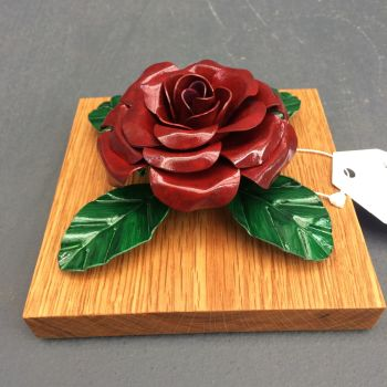 Dark red steel metal rose on an oak plaque suitable for wall hanging