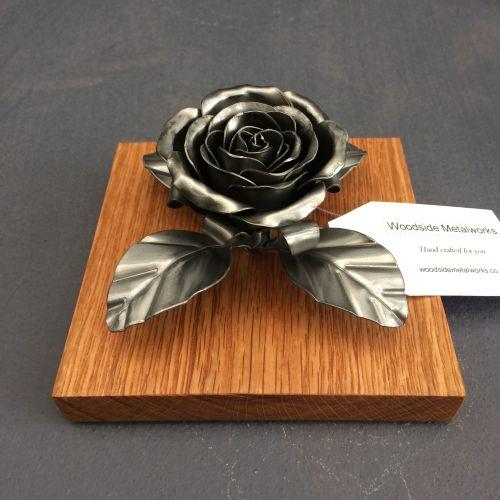 Steel metal rose on an oak plithe
