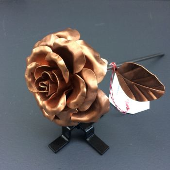 Elegant copper rose with leaves and a display stand