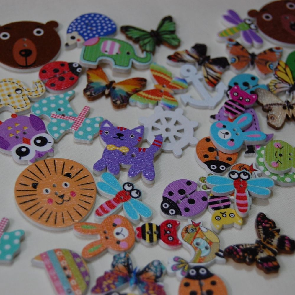 MIXED PACK OF 50 EMBELLISHMENTS/BUTTONS, VARIOUS DESIGNS.