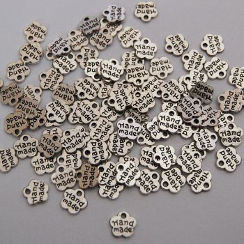 PACK OF 20 SILVER LOOK METAL FLOWERS WITH HAND MADE WORDING.
