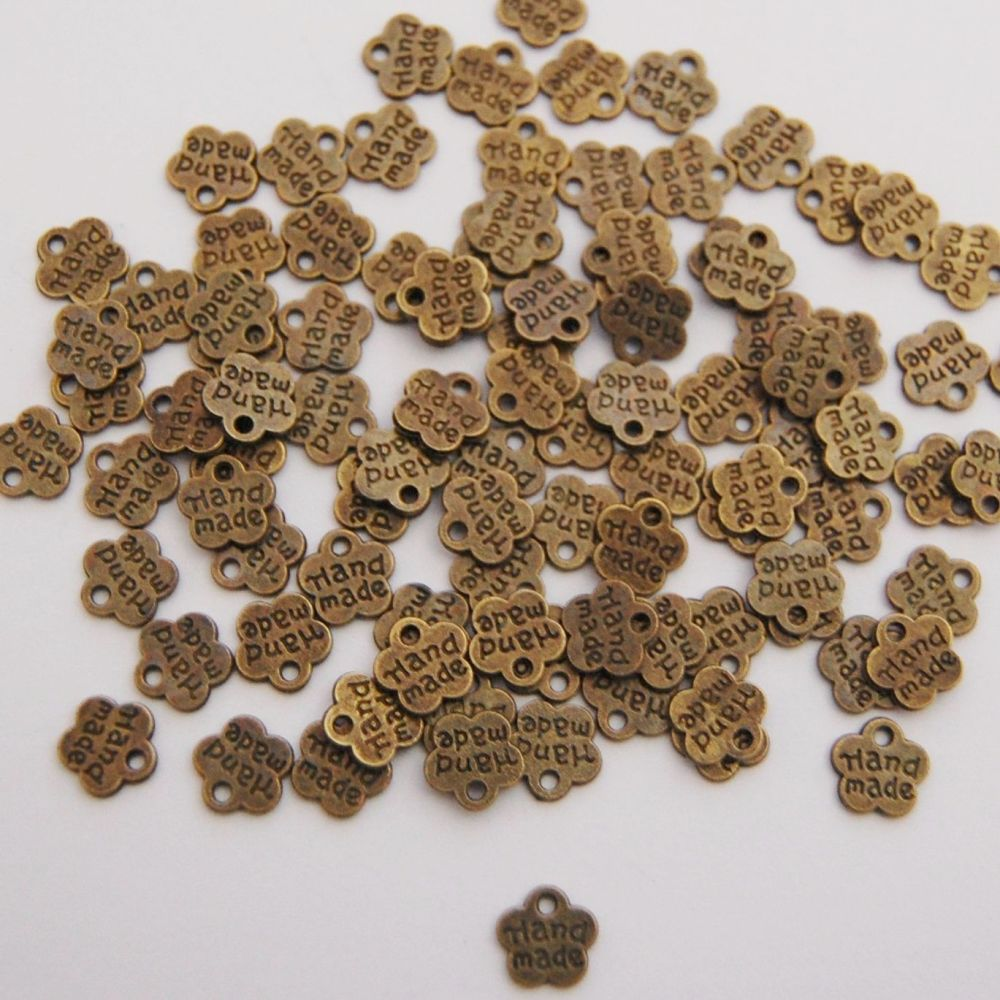 PACK OF 20 BRONZE LOOK METAL FLOWERS WITH HAND MADE WORDING.