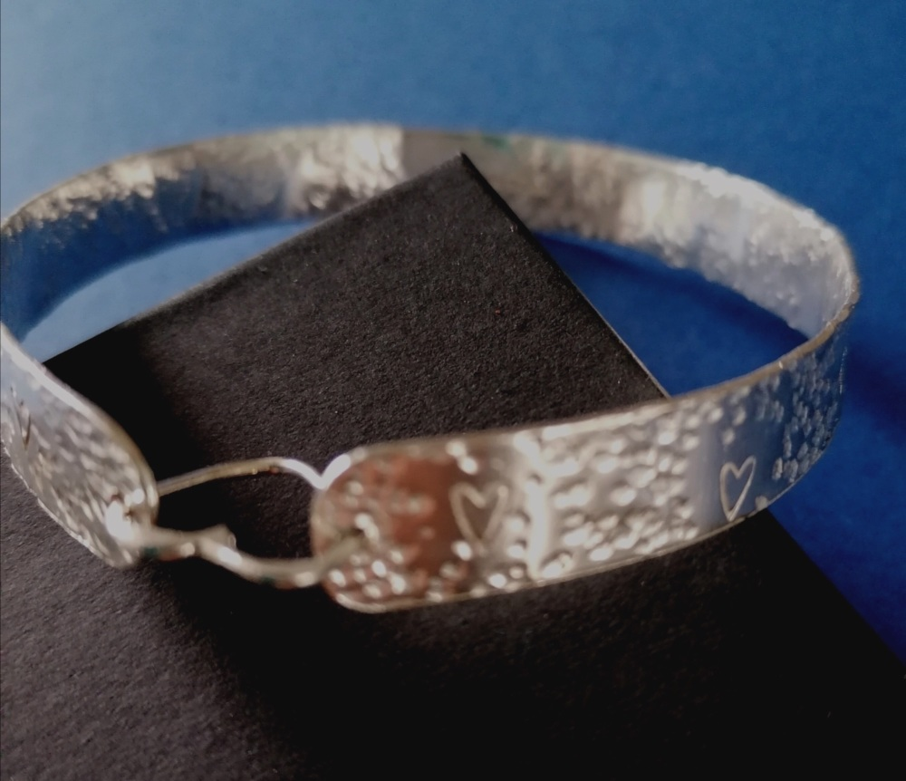 Hammered Sterling silver bangle with embossed hearts