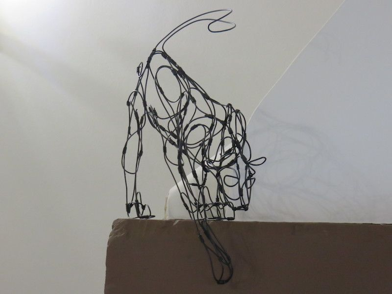 wire cat on fireplace shelf