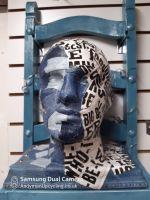Head decorated in half denim, half newsprint