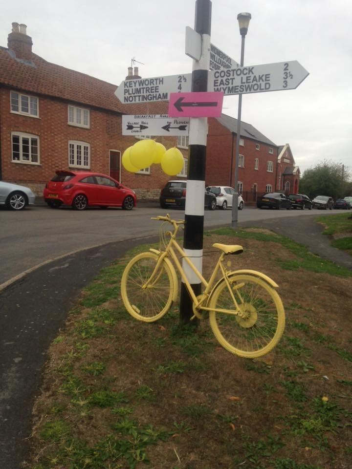 yellow-tour-bike-by-village-sign