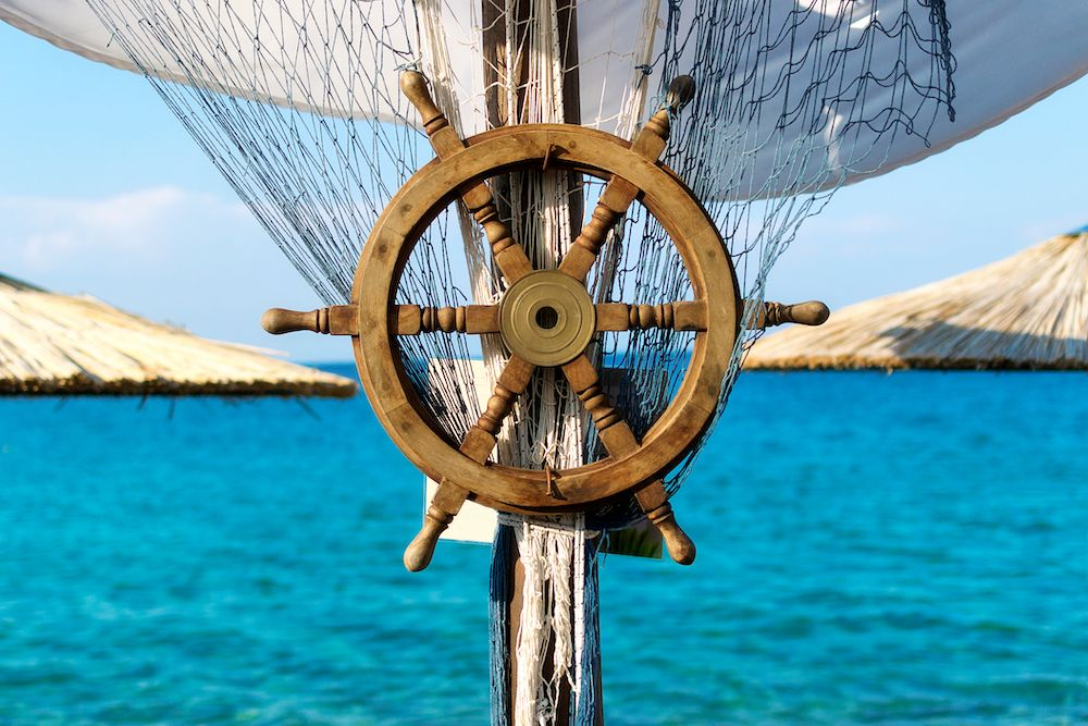 Canva - Wooden ship steering wheel and fishing net on the blue sea and sky