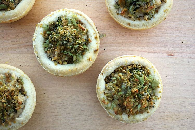 broccoli and vegan ricotta tartlets on a wood surface