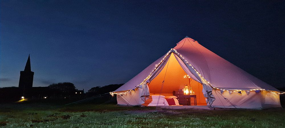 Bell-tent-glamping-at-Warren-Farm-Wales---bell-tent-and-church-spire-as-dar